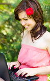 Young woman is playing on laptop. Outdoor shoot Stock Photo