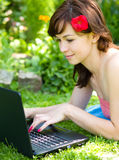 Young woman is playing on laptop. Outdoor shoot Stock Image