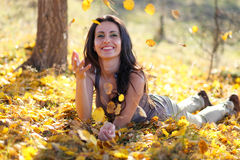 Young woman playing with leafs. Happy girl laying on the ground and throwing leafs in the air Royalty Free Stock Photos