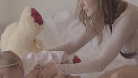 Young woman playing with a little baby girl sitting on the bed. The joys of motherhood. Loving family at home. Beautiful stock video