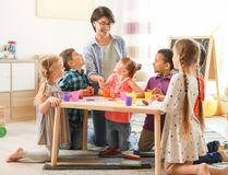 Young woman playing with little children royalty free stock images
