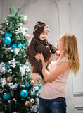 Young woman playing with little son dressed in monkey costume. Young women playing with little son dressed in monkey costume beside Christmas tree Stock Photography