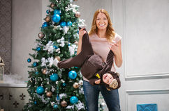 Young woman playing with little son dressed in monkey costume. Young women playing with little son dressed in monkey costume beside Christmas tree Stock Photos