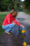 Young woman playing an maple leaf in puddle Royalty Free Stock Photos