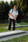Young woman playing mini golf. Young woman concentrating and playing mini golf royalty free stock photos