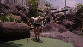 A young woman playing mini golf. In 4K stock footage