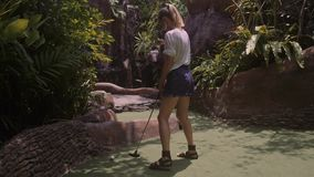 A young woman playing mini golf. In 4K stock video