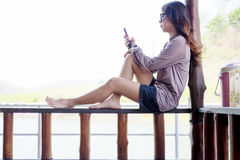 Young woman playing mobile phone while sitting wooden balcony on Royalty Free Stock Photo