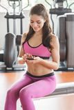 Young woman playing mobilephone while take a break during workou. Portrait of young man playing mobilephone while take a break during workout at the gym Stock Photo