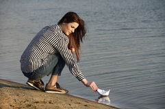Young woman playing with paper boat Stock Images