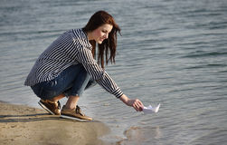 Young woman playing with paper boat Stock Image