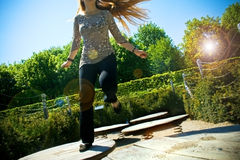 Young woman playing in park. (lens flare effect added Royalty Free Stock Image