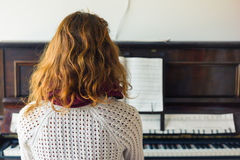 Young woman playing the piano Stock Image