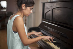 Young woman playing piano. Portrait of young woman playing old piano Stock Photography