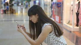 Young woman playing Pokemon GO indoor at shopping center, using smart phone. Girl play the popular smartphone game - stock video footage