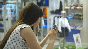 Young woman playing Pokemon GO indoor at shopping center, using smart phone. Girl play the popular smartphone game -. Catching pokemon in hypermarket mall stock video footage