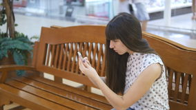 Young woman playing Pokemon GO indoor at shopping center, using smart phone. Girl sit at bench play the popular. Smartphone game - catching pokemon in stock video footage
