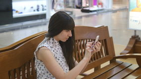 Young woman playing Pokemon GO indoor at shopping center, using smart phone. Girl sit at bench play the popular. Smartphone game - catching pokemon in stock video