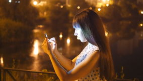 Young woman playing Pokemon GO outdoor at night, using smart phone. Girl play the popular smartphone game - catching. Pokemon in park at evening stock footage