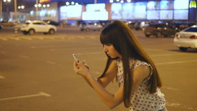 Young woman playing Pokemon GO outdoor at shopping center parking, using smart phone. Girl in evening play the popular. Smartphone game - catching pokemon stock video
