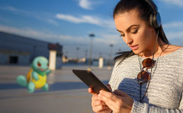 Young woman playing pokemon go on tablet Stock Image