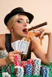 Young woman playing poker. With cigar in hand Royalty Free Stock Photos