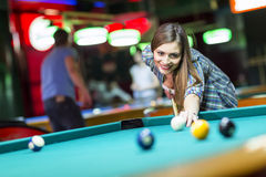 Young woman playing pool. In a bar Royalty Free Stock Images
