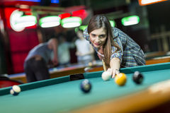 Young woman playing pool. View of the young woman playing pool Royalty Free Stock Photo