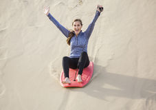 Young Woman Playing in the Sand Dunes Outdoor Lifestyle. An excited and happy young woman riding a board down a sand dune hill having fun playing outdoors while Royalty Free Stock Images