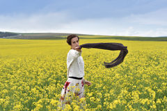 Young woman playing with scarf in a canola field Stock Image