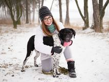 Young woman playing snow winter outdoors hugging cute adopted blind setter dog. Kindness and humanity concept. Young lady playing snow winter outdoors hugging stock image