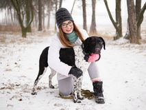 Young woman playing snow winter outdoors hugging cute adopted blind setter dog. Kindness and humanity concept. Young lady playing snow winter outdoors hugging Royalty Free Stock Photo