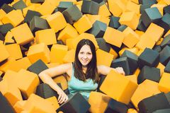 Young woman playing with soft blocks at indoor children playground in the foam rubber pit in the trampoline center royalty free stock photography