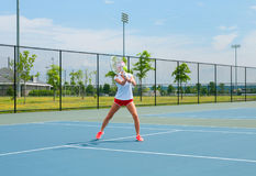 Young woman is playing tennis on the tennis court Royalty Free Stock Photography