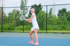 Young woman is playing tennis on the tennis court Stock Image