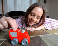 Young Woman, playing with toy truck. A young woman playing with a red toy truck stock photos