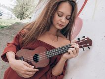 Young woman playing on ukulele stock photo