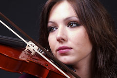 Young woman playing the violin. A close up of a young woman playing the violin, set against a dark background Stock Photo