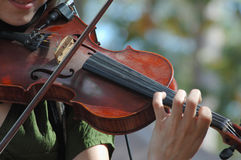 A young woman playing the violin. A young woman plays the violin outdoors in the sunlight Stock Image