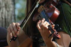 A young woman playing the violin. A young woman plays the violin outdoors in the sunlight Stock Photos