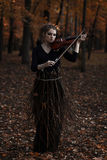 Young woman playing violin in the fall park Stock Photo