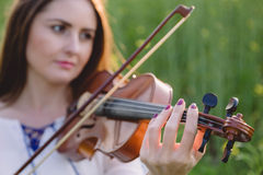 Young woman playing violin in a field at sunset. Young woman playing violin in a green field at sunset Royalty Free Stock Images