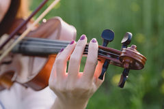 Young woman playing violin in a field at sunset. Young woman playing violin in a green field at sunset. Focus on the hand Royalty Free Stock Images