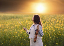 Young woman playing violin in a field at sunset Royalty Free Stock Photography