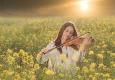 Young woman playing violin in a field at sunset Royalty Free Stock Photos