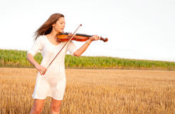 Young woman playing violin outdoors. On the field in summer evening Stock Images