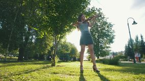 Young woman playing a violin standing on the grass in the park at sunset stock footage