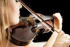 A young woman playing a violin. A violinist playing a violin or fiddle on a dark background Royalty Free Stock Images