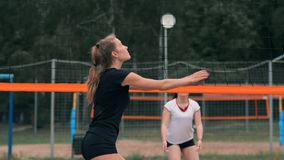 Young woman playing volleyball on the beach in a team carrying out an attack hitting the ball. Girl in slow motion hits stock footage