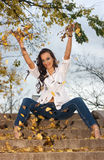 Young woman playing with yellow leaves. Young woman throwing up autumnal leaves in the air royalty free stock photo